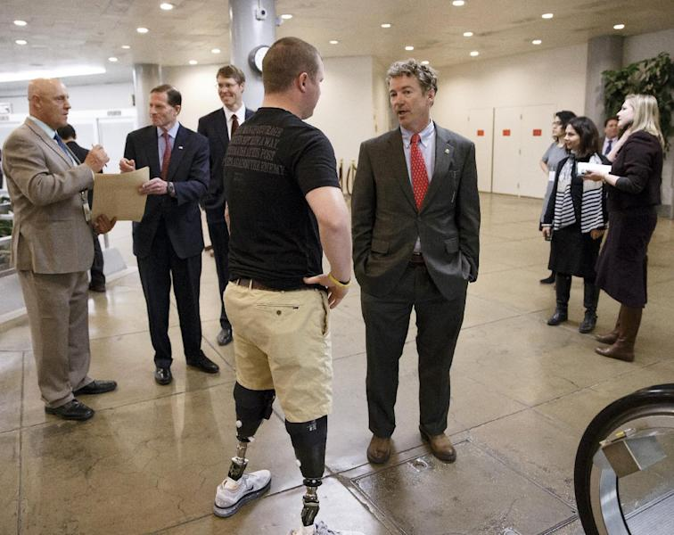 Sen. Rand Paul, R-Ky., a member of the Senate Foreign Relations Committee, center, stops to speak to a wounded military veteran as he and other lawmakers make their way to the chamber to advance a bill providing $1 billion in loan guarantees to Ukraine as President Barack Obama meets with U.S. allies in Europe to punish Moscow for its annexation of the Crimean peninsula, at the Capitol in Washington, Monday, March 24, 2014. (AP Photo/J. Scott Applewhite)