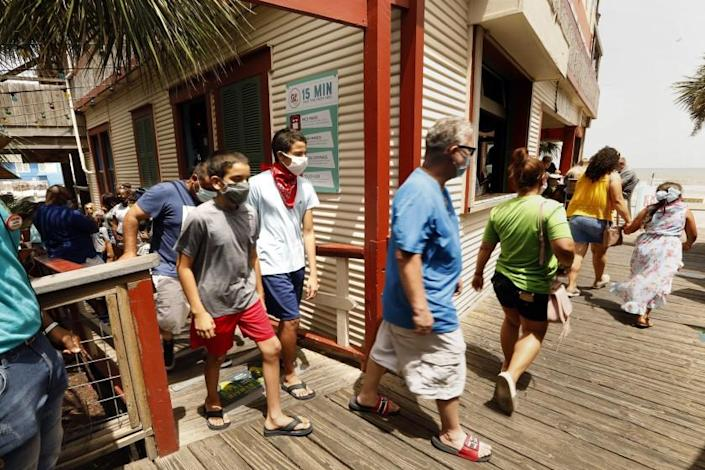 GALVESTON, TEXAS-JULY 3, 2020-Customers comply with the mandatory face mask order at The Spot, a popular restaurant and bar on the boardwalk in Galveston Beach. The beaches are closed on Galveston island for the 4th of July weekend, and there is a mandatory mask order in place, but that hasn't stopped people from visiting this beach city. (Carolyn Cole/Los Angeles Times)
