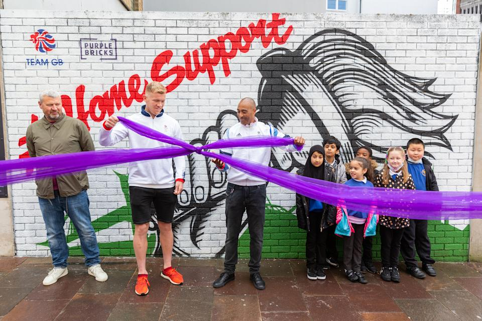 Jackson unveils the Purplebricks Home Support mural in Cardiff alongside rugby sevens star Sam Cross, pupils from Ninian Park Primary School and the mural artist Bradley Woods