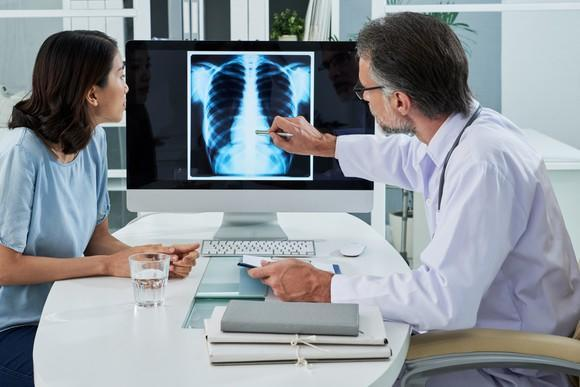Doctor showing a chest x-ray on a computer to a patient
