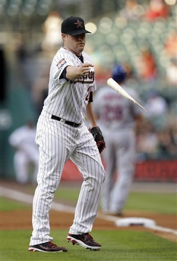 Houston Astros' Bud Norris tosses the broken bat of New York Mets' Daniel Murphy after Murphy grounded out to end the first inning of a baseball game Monday, April 30, 2012, in Houston. (AP Photo/David J. Phillip)