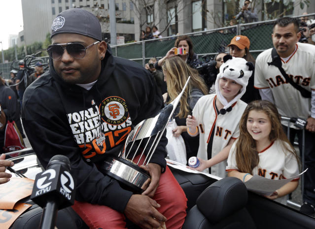 San Francisco Giants Pablo Sandoval holds the MVP trophy as kids wait for his autograph before the start of the victory parade in San Francisco, Wednesday, Oct. 31, 2012. The Halloween Day World Series victory parade is perfectly suited for the hundreds of thousands of orange-and-black-clad Giants fans expected to flood into the city. The team's second championship in three years will head down Market Street Wednesday afternoon and end with a celebration in front of City Hall. (AP Photo/Marcio Jose Sanchez)