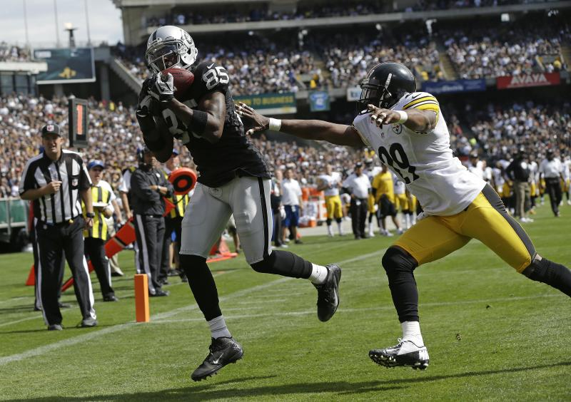 Oakland Raiders wide receiver Darrius Heyward-Bey, left, catches a three-yard pass for a touchdown as Pittsburgh Steelers free safety Ryan Mundy, right, looks on during the second quarter of an NFL football game in Oakland, Calif., Sunday, Sept. 23, 2012. (AP Photo/Marcio Jose Sanchez)