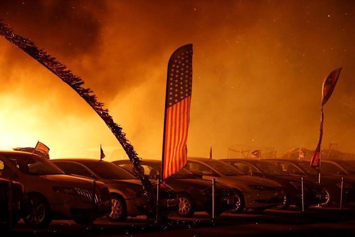 An American flag is seen at an engulfed car dealership during the Camp Fire in Paradise, Calif., on Nov. 8.