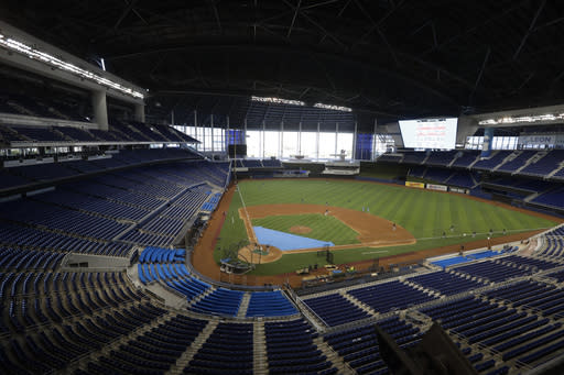FILE - This is a July 4, 2020, file photo showing the Miami Marlins running drills during a baseball workout at Marlins Park in Miami. Marlins Park will have a new look for its 2020 season debut Friday, thanks to cozier dimensions and a switch to artificial turf. Also, the home team is in first place. (AP Photo/Wilfredo Lee, File)