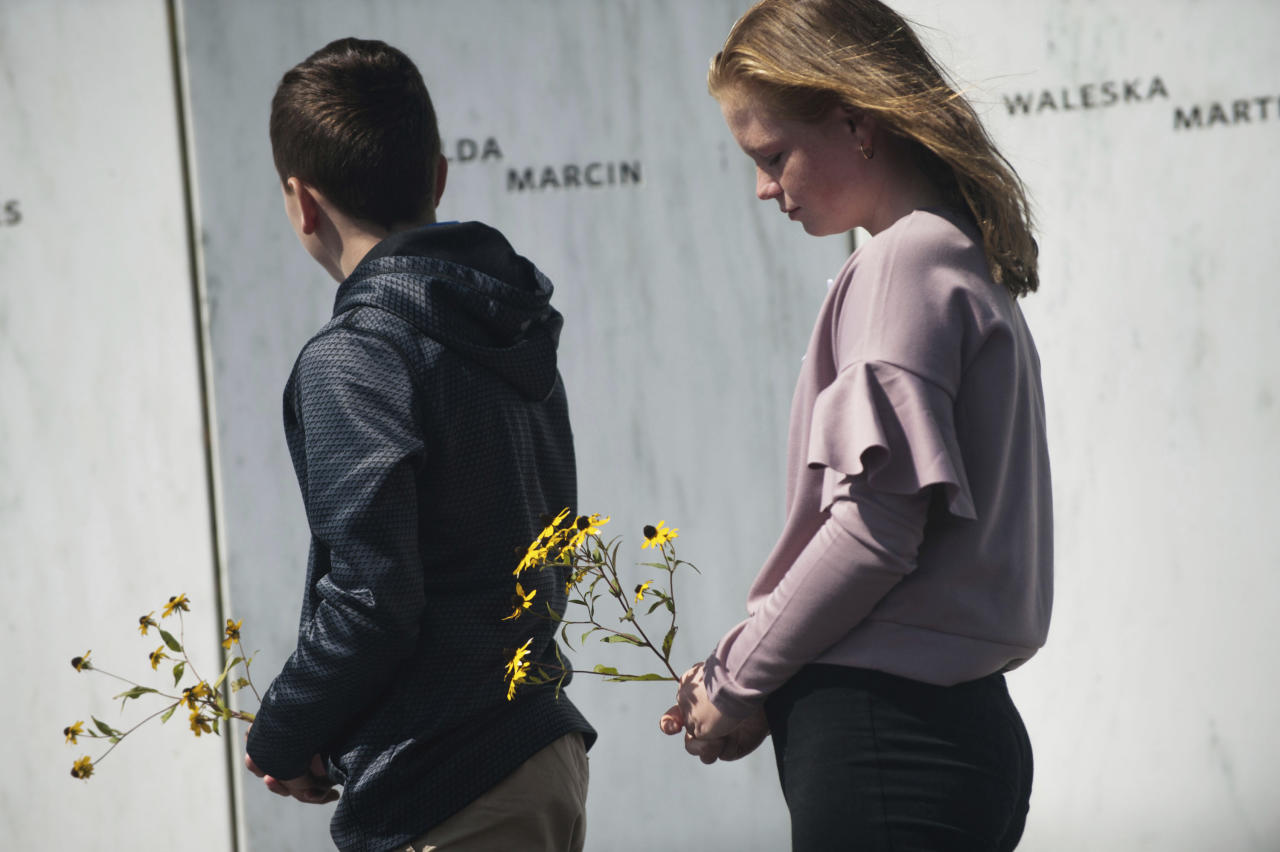 """Everett Lata, left, 13, and his sister Ellie, right, 12, of Saylorsburg, Pa., place flowers by the name of their great-grandmother Hilda Marcin along the Wall of Names on Monday, Sept. 11, 2017 at the Flight 93 National Memorial in Shanksville, Pa. """"It's truly something special,"""" said Everett of visiting the site. """"I hope that nothing like this would ever happen again,"""" said Ellie. (Stephanie Strasburg/Pittsburgh Post-Gazette via AP)"""