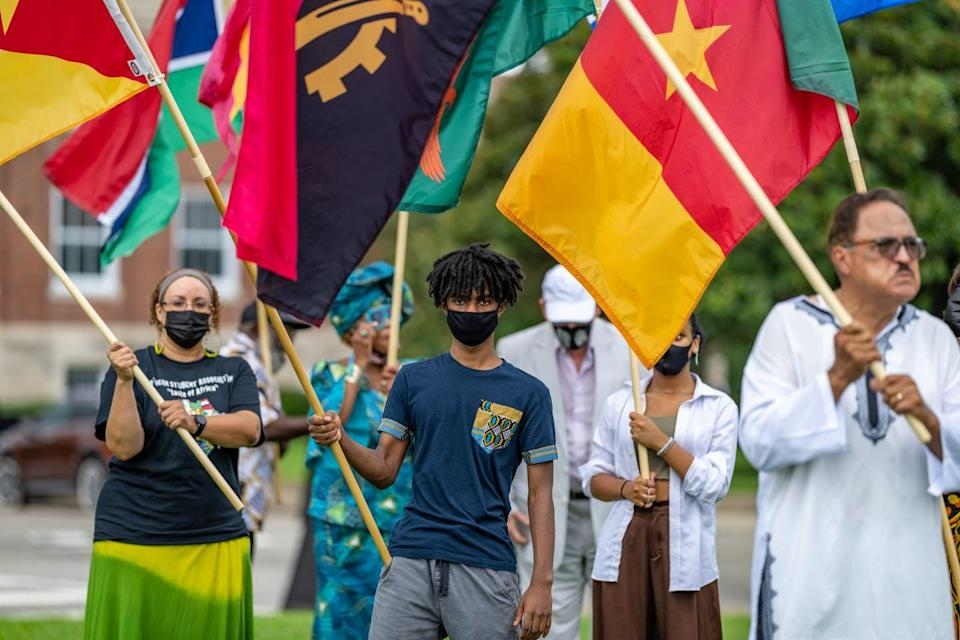 A group of people march, wearing masks and holding flags.
