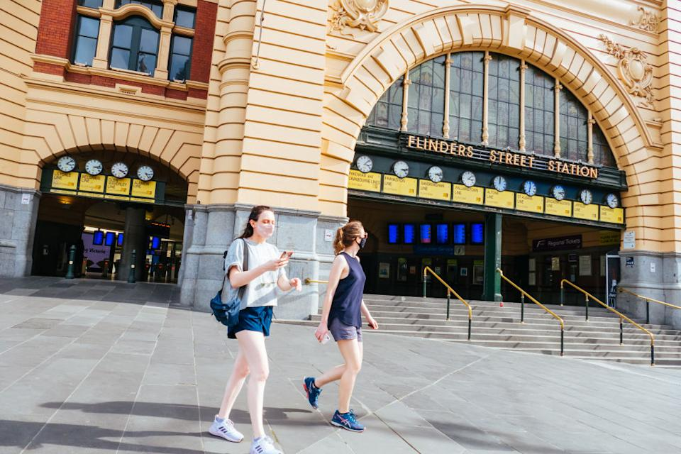 People wearing masks in front of Flinders St Station, which is quiet and empty during the coronavirus pandemic.