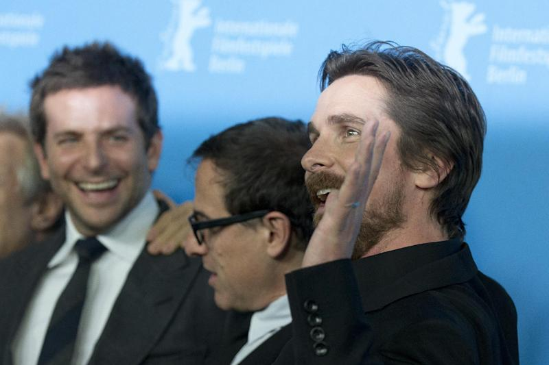 Actor Christian Bale, right, waves at photographers during the photo call for the film American Hustle during the International Film Festival Berlinale, in Berlin, Friday, Feb. 7, 2014. (AP Photo/Axel Schmidt)