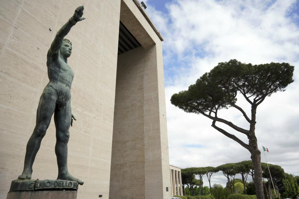 """FILE - In this Monday, May 6, 2019 file photo, a bronze sculpture by Italo Griselli, known under the Fascist regime as """"Saluto Fascista"""" (Fascist Salute) and after the war renamed Genio dello Sport (Genius of Sport), stands at the entrance of a fascist architecture building in the EUR neighborhood, in Rome. An extreme-right political party's violent exploitation of anger over government anti-pandemic restrictions is forcing Italy to wrestle with its fascist legacy and fueling fears that there could be a replay of last week's mobs trying to force their way toward Parliament.. (AP Photo/Andrew Medichini)"""