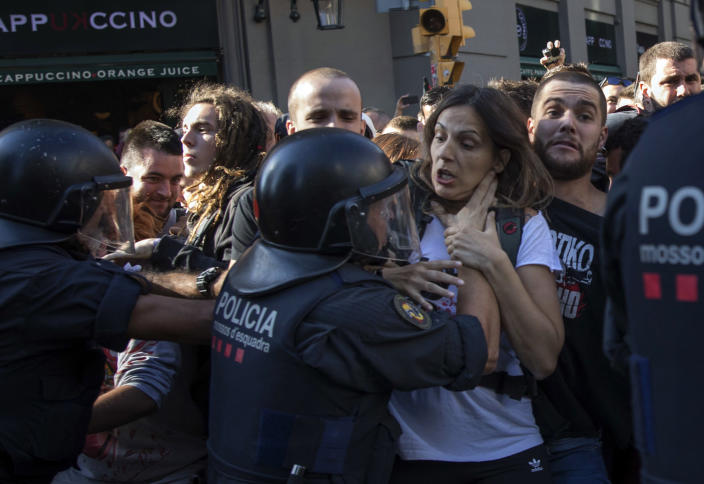 Catalan police officers clash with pro independence demonstrators on their way to meet demonstrations by members and supporters of National Police and Guardia Civil in Barcelona on Saturday, Sept. 29, 2018. (AP Photo/Emilio Morenatti)