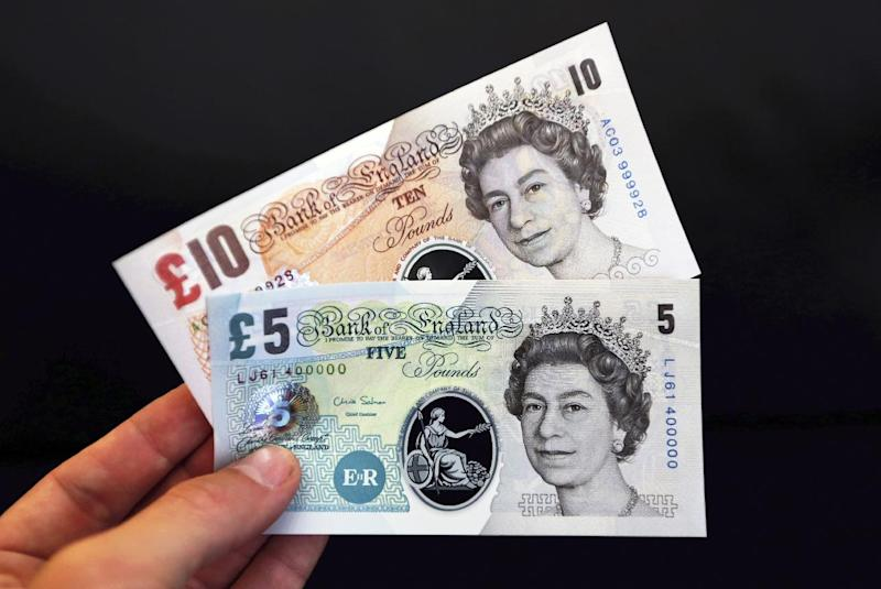 """A sample the proposed new British banknotes made of a polymer, five pound and ten pound notes held for an arranged photograph during a news conference at the Bank of England in London, Tuesday, Sept. 10, 2013. Bank of England Deputy Governor Charlie Bean, said: """"Polymer banknotes are cleaner, more secure and more durable than paper money"""", but the bank said Tuesday it will hold public consultations to consider the change. (AP Photo / Chris Ratcliffe)"""