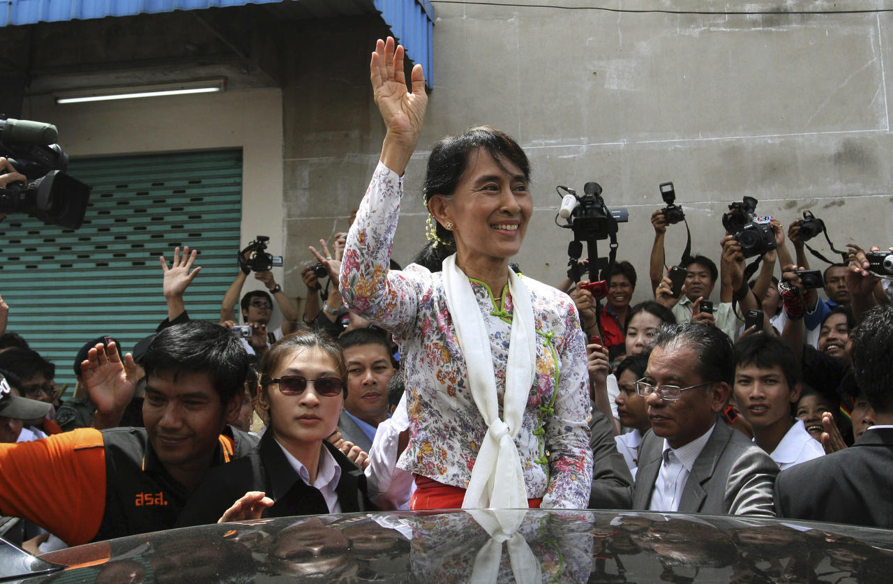 Myanmar opposition leader Aung San Suu Kyi waves while leaving a community center in Samut Sakhon Province, Thailand on Wednesday, May 30, 2012. Kicking off her first trip abroad in nearly a quarter-century, Suu Kyi offered encouragement Wednesday to impoverished Myanmar migrants whose flight to neighboring Thailand is emblematic of the devastation wrought on her homeland by decades of misrule.(AP photo/Sakchai Lalit)