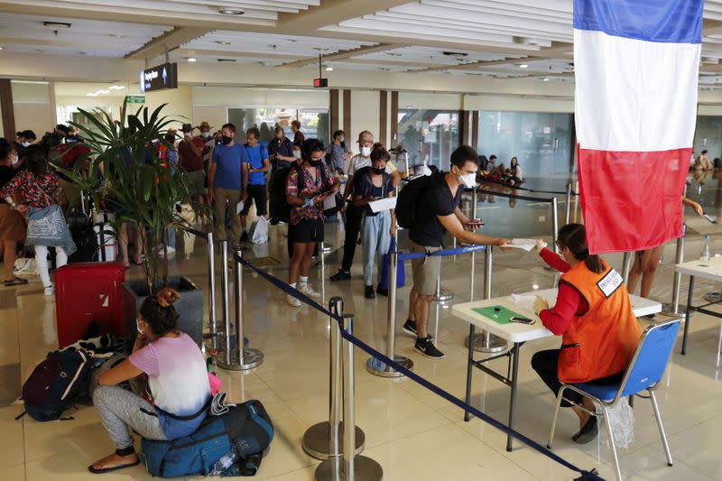 Visitors queue to register their documents before their chartered flight back to their country at Ngurah Rai International Airport in Bali