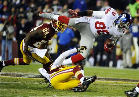 Dec 1, 2013; Landover, MD, USA; New York Giants wide receiver Hakeem Nicks (88) is tackled by Washington Redskins safety Brandon Meriweather (31) during the second half at FedEx Field. The Giants won 24 - 17. Mandatory Credit: Brad Mills-USA TODAY Sports