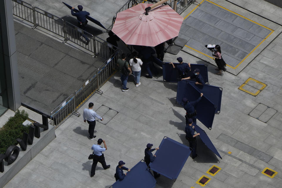 Security guards move barriers intended for us to block off protesters outside the Evergrande headquarters in Shenzhen, China, Friday, Sept. 24, 2021. Things appeared quiet at the headquarters of the heavily indebted Chinese real estate developer Evergrande, one day after the day it had promised to pay interest due to bondholders in China. (AP Photo/Ng Han Guan)