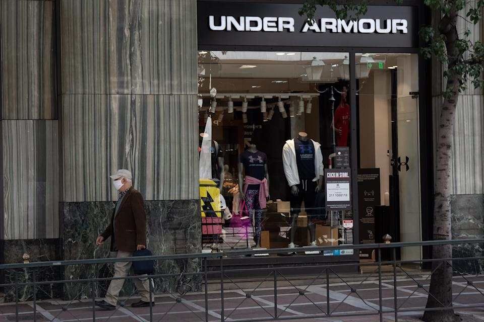 ATHENS, GREECE - 2021/04/21: A man walking past the Under Armour store at Syntagma square. (Photo by Nikolas Joao Kokovlis/SOPA Images/LightRocket via Getty Images)