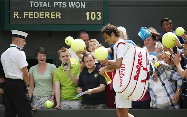 Roger Federer of Switzerland signs autographs after beating Paolo Lorenzi of Italy during their first round match at the All England Lawn Tennis Championships in Wimbledon, London, Tuesday, June 24, 2014. (AP Photo/Pavel Golovkin)