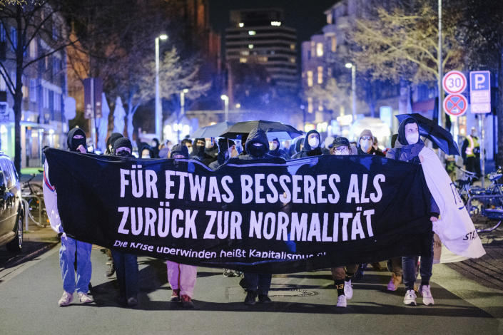 """Participants in a demonstration against curfew restrictions walk through Nordstadt with a banner reading """"For something better than back to normal"""" during the nightly curfew, in Hanover, Germany, Saturday, April 24, 2021. Federal coronavirus emergency curfew regulations have been in effect as of Saturday. This includes, among other things, curfew restrictions between 10 p.m. and 5 a.m. (Ole Spata/dpa via AP)"""