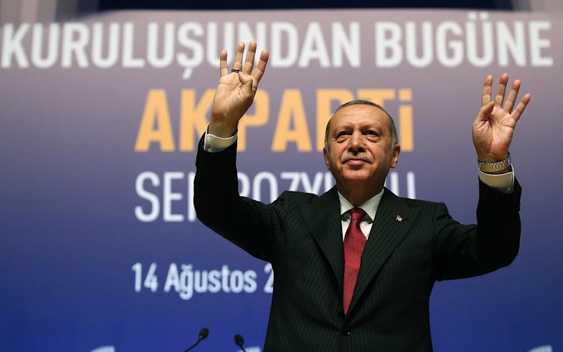 Recep Tayyip Erdogan gestures while addressing at a symposium at the ATO Congresium Hall in Ankara - Anadolu
