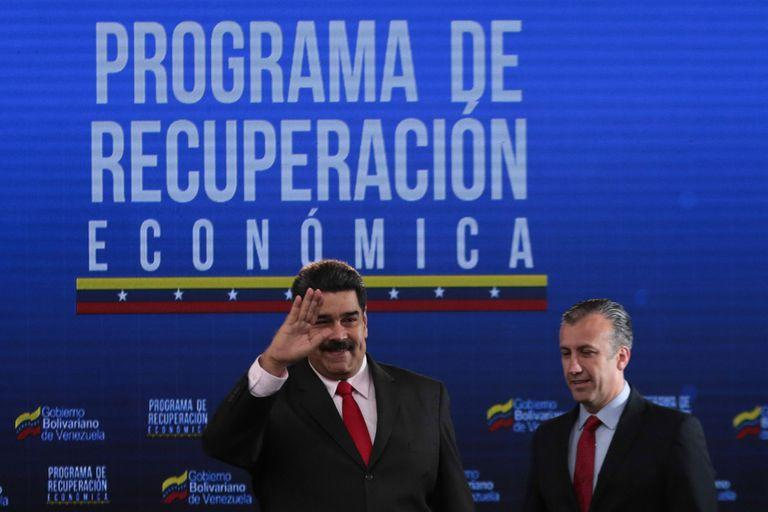 This handout picture released by the Venezuelan Presidency shows President Nicolas Maduro (L) gesturing next to Minister of Industries and National Production Tareck El Aissami, during a meeting with Venezuelan businessmen at the Miraflores presidential palace in Caracas on September 5, 2018. (Photo