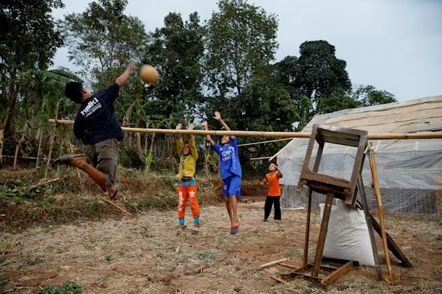"Children play volleyball at an abandoned rice field in Cikawao village of Majalaya, West Java province, Indonesia, September 21, 2017. REUTERS/Beawiharta SEARCH ""BOAR FIGHT"" FOR THIS STORY. SEARCH ""WIDER IMAGE"" FOR ALL STORIES."