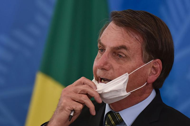 Brazil's President Jair Bolsonaro removes his mask to speak to journalists after a March 18 press conference on the new coronavirus at the Planalto Presidential Palace in Brasilia. (Photo: Andre Borges/ASSOCIATED PRESS)