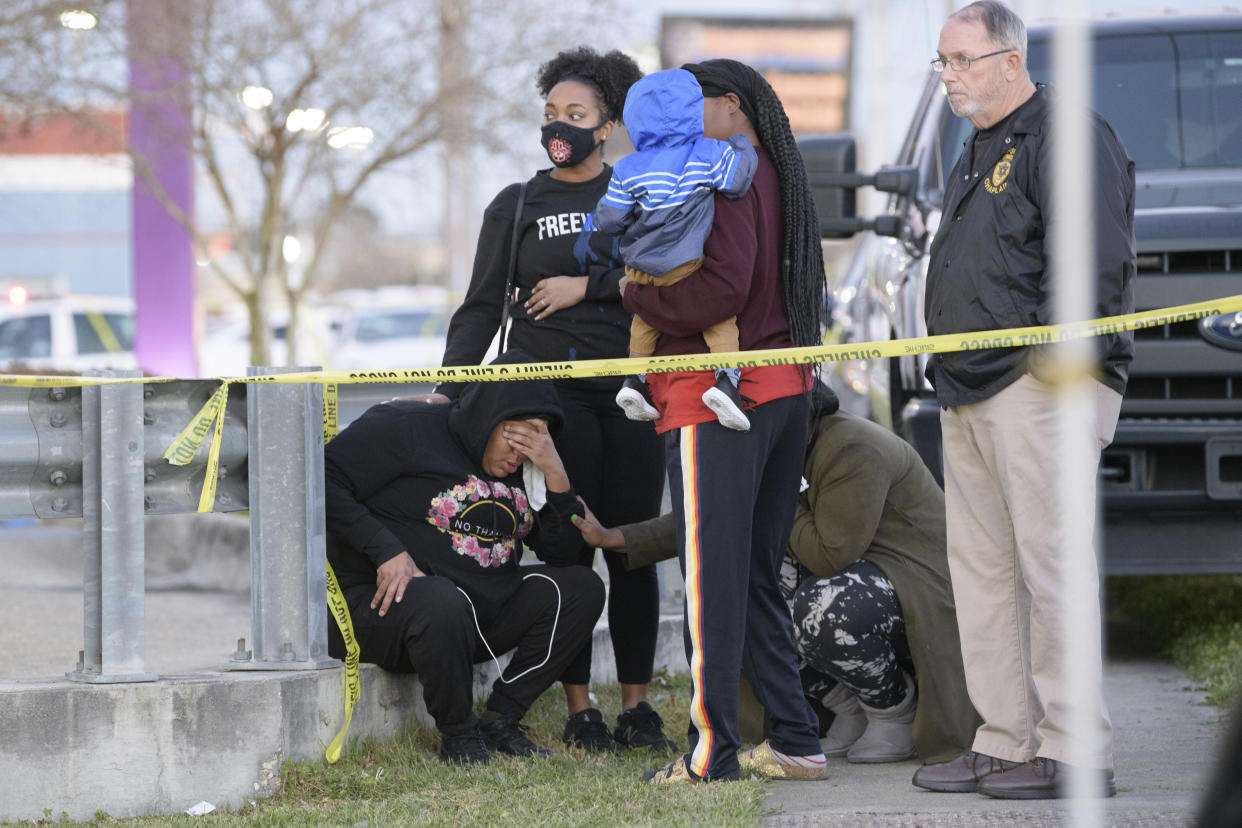 People react at the scene of a multiple fatality shooting at the Jefferson Gun Outlet in Metairie, La. Saturday, Feb. 20, 2021. A person went into a gun store and shooting range in a New Orleans suburb and fatally shot two people Saturday, causing customers and staff to open fire on the shooter, said a sheriff. The shooter also died.(AP Photo/Matthew Hinton)