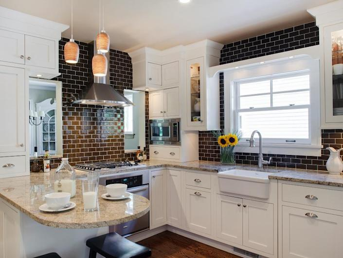 <p>A dark brown backsplash keeps this kitchen from looking too stuffy or boring. It not only blends beautifully with the countertops and flooring, but the contrast with the stark white cabinetry adds a gorgeous balance that keeps the space interesting and warm. </p>