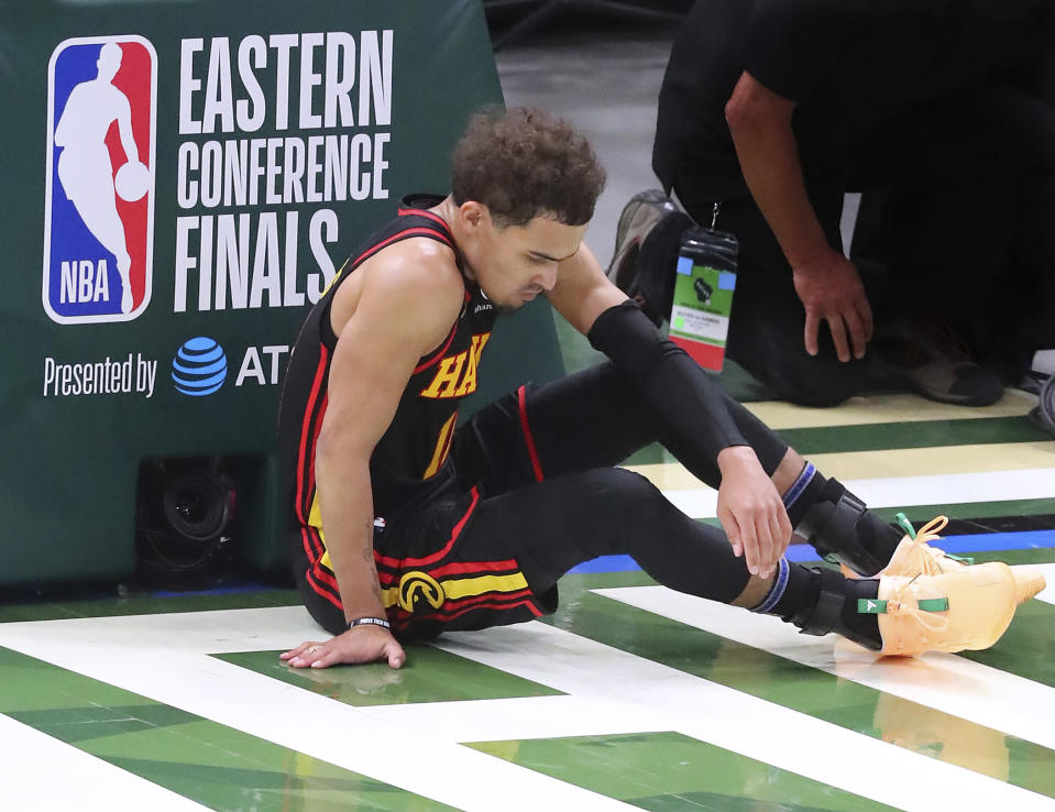 Atlanta Hawks guard Trae Young sits on the court after turning the ball over to Milwaukee Bucks center Boork Lopez during the second quarter of Game 2 of the NBA Eastern Conference basketball finals game Friday, June 25, 2021, in Milwaukee. (Curtis Compton/Atlanta Journal-Constitution via AP)
