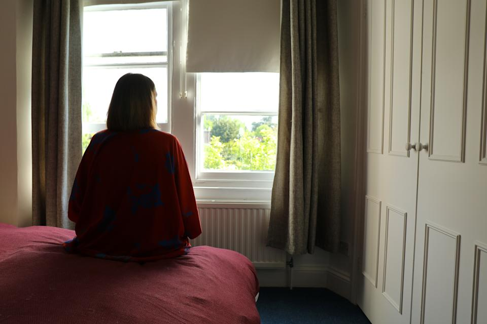 Rear view of a caucasian woman seated on the bedroom during lockdown coronavirus
