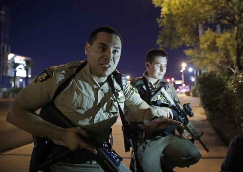 FILE - In this Oct. 1, 2017, file photo, police officers advise people to take cover near the scene of a shooting near the Mandalay Bay resort and casino on the Las Vegas Strip in Las Vegas. Police in Las Vegas promised to release dispatch logs and additional officer reports on Wednesday, May 23, 2018, providing more witness accounts of the chaos, carnage and compassion during the deadliest mass shooting in modern U.S. history. The scheduled release of documents follows a court order in a public records lawsuit by The Associated Press and other media organizations seeking information about the Oct. 1 shooting. (AP Photo/John Locher, File)