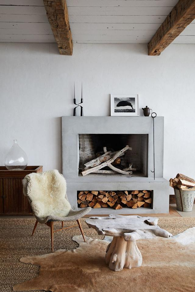 <p>The recipe for a Scandinavian-inspired room: Sheepskin, minimalist decor, and natural furniture. This streamlined fireplace is the perfect fit for a modern, thoughtfully curated, and layered living room. The built-in wood storage compartment is also super h handy. </p>