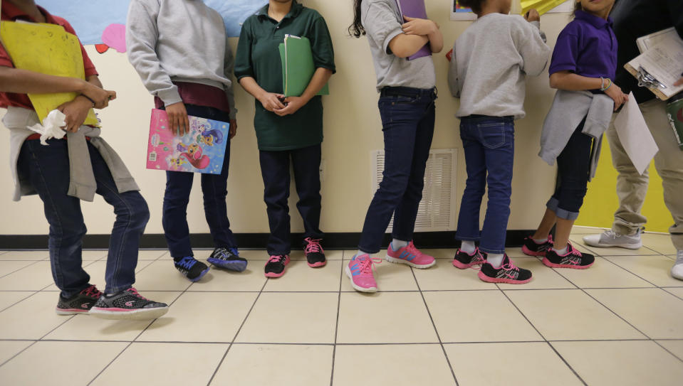 """FILE - In this Aug. 29, 2019, file photo, migrant teens line up for a class at a """"tender-age"""" facility for babies, children and teens, in Texas' Rio Grande Valley, in San Benito, Texas. A federal volunteer at the Biden administration's largest shelter for unaccompanied immigrant children says paramedics were called regularly during her the two weeks she worked there. She said panic attacks would occur often after some of the children were taken away to be reunited with their families, dashing the hopes of those left behind. The conditions described by the volunteer highlight the stress of children who cross the U.S.-Mexico border alone and now find themselves held at unlicensed mass-scale facilities waiting to reunite with relatives. (AP Photo/Eric Gay File)"""