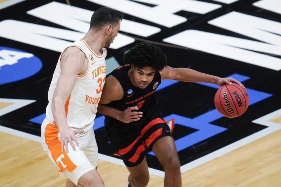 Oregon State guard Ethan Thompson (5) drives on Tennessee forward Uros Plavsic (33) during the first half of a first round game at Bankers Life Fieldhouse in the NCAA men's college basketball tournament in Indianapolis, Friday, March 19, 2021. (AP Photo/Paul Sancya)