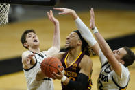 Minnesota forward Brandon Johnson, center, drives to the basket between Iowa forward Patrick McCaffery, left, and forward Jack Nunge, right, during the first half of an NCAA college basketball game, Sunday, Jan. 10, 2021, in Iowa City, Iowa. (AP Photo/Charlie Neibergall)