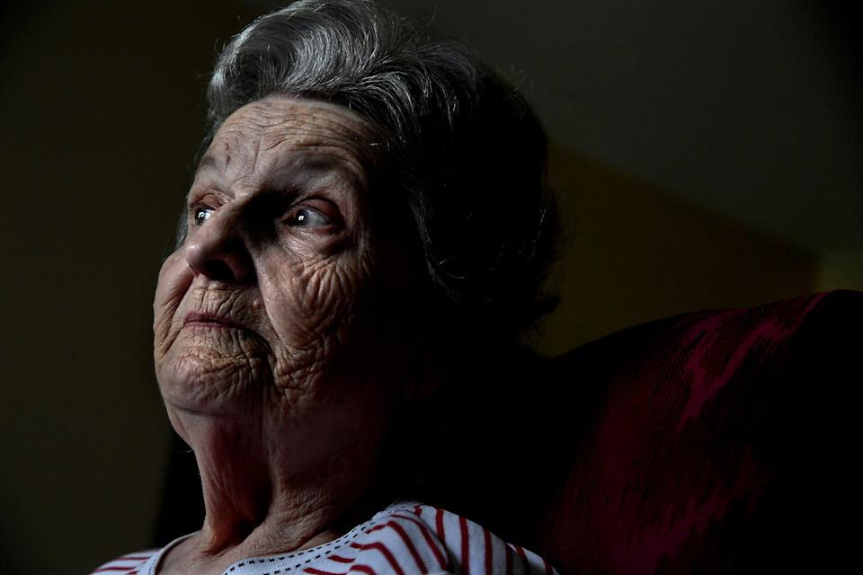 An older woman looks into the distance.