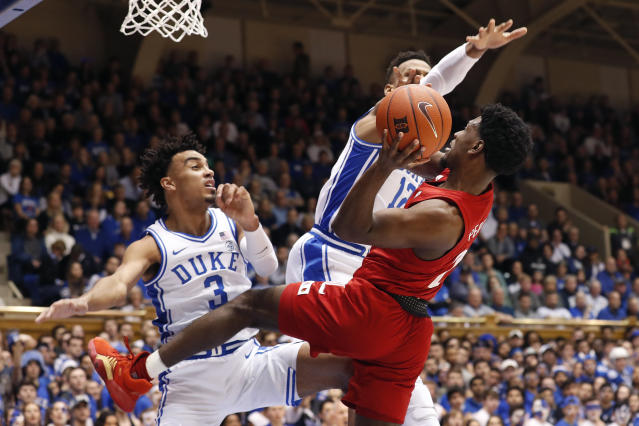 Duke guard Tre Jones (3) and forward Javin DeLaurier (12) defend against Louisville guard Darius Perry (2) during the first half of an NCAA college basketball game in Durham, N.C., Saturday, Jan. 18, 2020. (AP Photo/Gerry Broome)