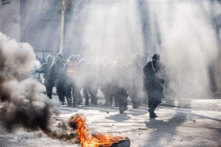Smoke rises near the police as anti-government protesters hold a demonstration in Tuzla February 6, 2014. REUTERS/Edmond Ibrahimi