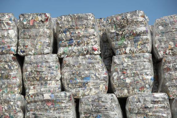 Sorted recycled materials sit in stacks outside of a recycling facility in Germany.