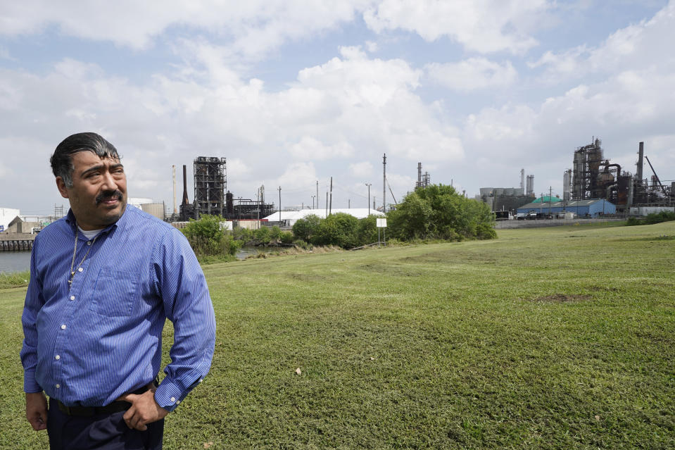FILE - In this Monday, March 23, 2020 file photo, Juan Flores stands in small park near a refinery along the Houston Ship Channel in Houston. Flores is working on a project to install air monitors at schools, not to warn children when the air was too bad to play outside, but alert them when plant emissions were low enough to make that safe. (AP Photo/David J. Phillip)