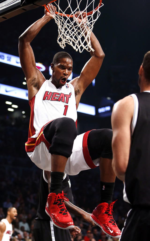Miami Heat's Chris Bosh celebrates after dunking the ball against the Brooklyn Nets during an NBA basketball game Friday, Nov. 1, 2013, in New York. (AP Photo/Jason DeCrow)