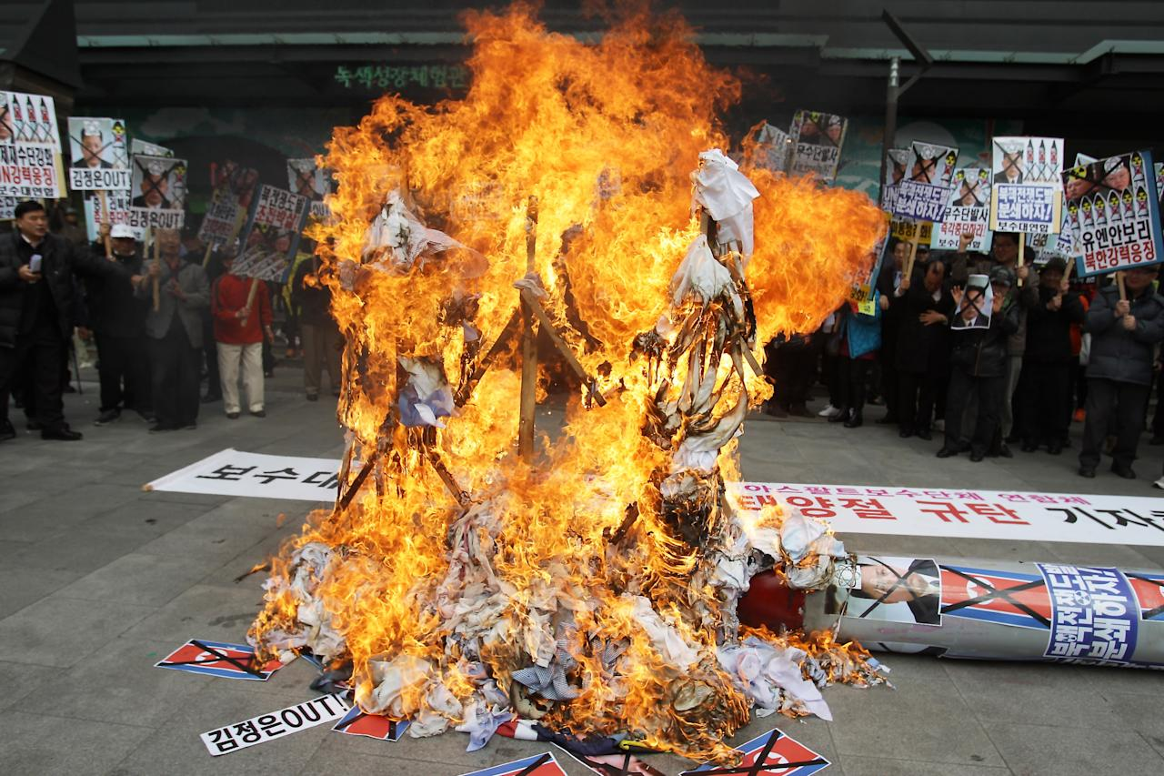 SEOUL, SOUTH KOREA - APRIL 15:  Flames spike up as South Korean conservative protesters stand by and burn a mockup of a North Korean missile and effigies of North Korea national founder Kim Il-Sung, former North Korean leader Kim Jong-Il and now leader Kim Jong-Un during an anti-North Korea rally on April 15, 2013 in Seoul, South Korea. North Korea marks its founder Kim Il-Sung's 101th birthday today while the fear on possible missile launch continues.  (Photo by Chung Sung-Jun/Getty Images)
