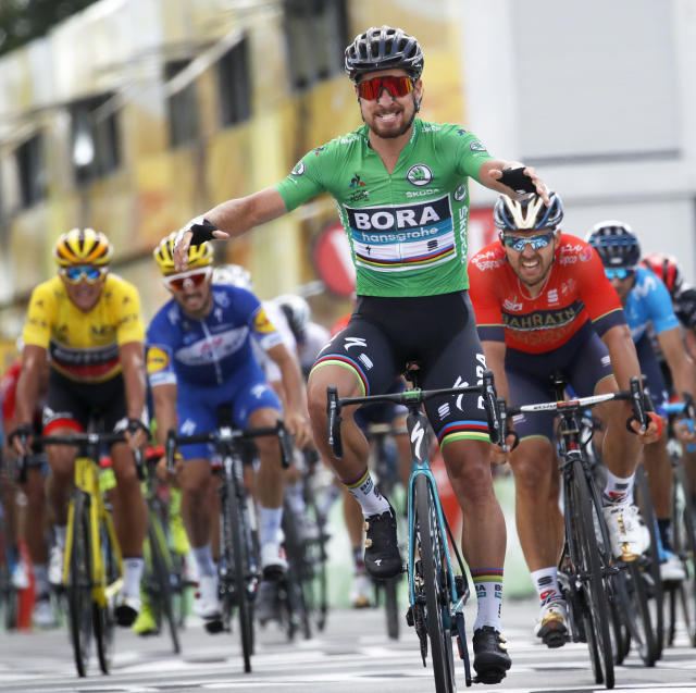 Slovakia's Peter Sagan, wearing the best sprinter's green jersey, crosses the finish line ahead of Italy's Sonny Colbrelli, second right, Belgium's Philippe Gilbert, second left, and Belgium's Greg van Avermaet, left, to win the fifth stage of the Tour de France cycling race over 204.5 kilometers (127 miles) with start in Lorient and finish in Quimper, France, Wednesday, July 11, 2018. (AP Photo/Christophe Ena)