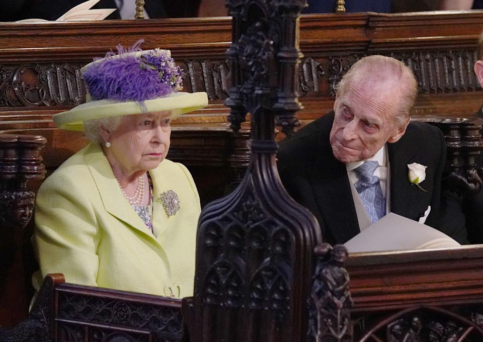 Britain's Queen Elizabeth II and Britain's Prince Philip, Duke of Edinburgh (R) during the wedding ceremony of Britain's Prince Harry, Duke of Sussex and US actress Meghan Markle in St George's Chapel, Windsor Castle, in Windsor, on May 19, 2018. (Photo by Jonathan Brady / POOL / AFP)        (Photo credit should read JONATHAN BRADY/AFP via Getty Images)