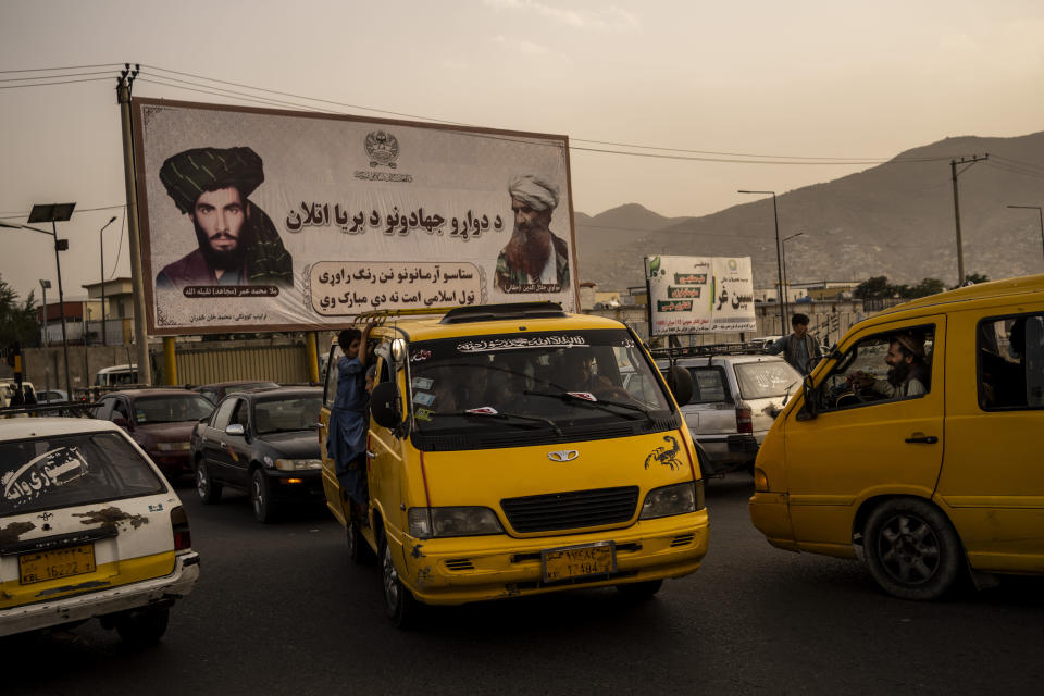 Vehicles drive past a mural paying homage to late Taliban founder Mullah Mohammad Omar, left, and the late founder of the feared Haqqani network, Jalaluddin Haqqani, in Kabul, Afghanistan, Saturday, Sept. 11, 2021. (AP Photo/Bernat Armangue)