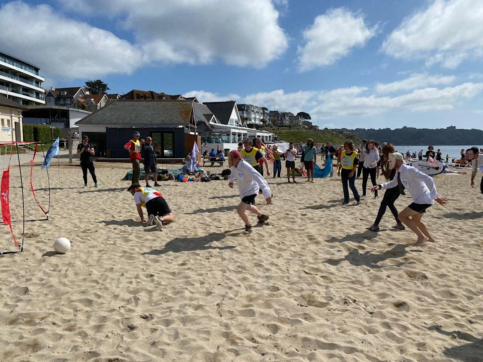 A pretend soccer match between environmental activists near Falmouth, England, on June 12, 2021. One side is wearing masks with the faces of G-7 leaders on them.