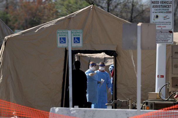 PHOTO: Healthcare professionals prepare to screen people for the coronavirus at a testing site erected by the Maryland National Guard in a parking lot at FedEx Field, March 30, 2020, in Landover, Md. (Chip Somodevilla/Getty Images)