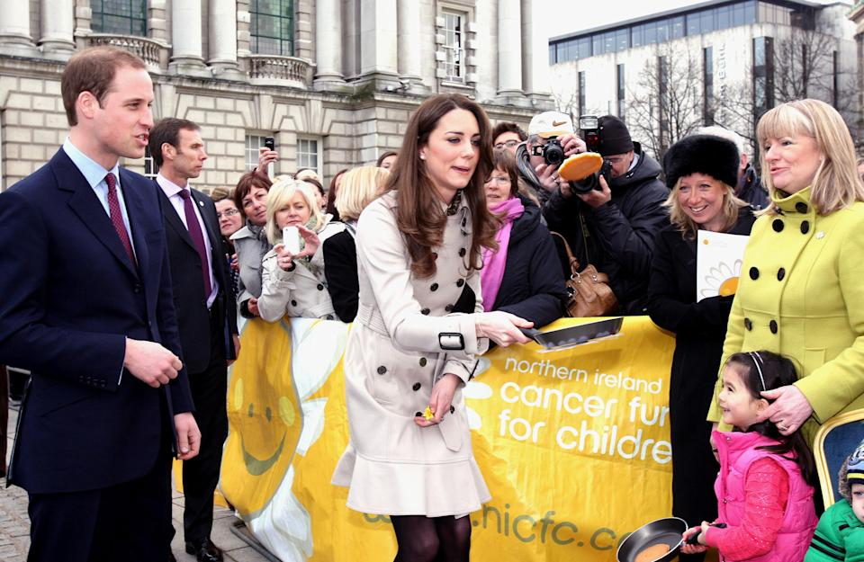 Prince William watches as Kate Middleton flips a pancake during a Northern Ireland Cancer Fund for Children event outside Belfast City Hall, during their visit to Northern Ireland.   (Photo by Paul Faith/PA Images via Getty Images)