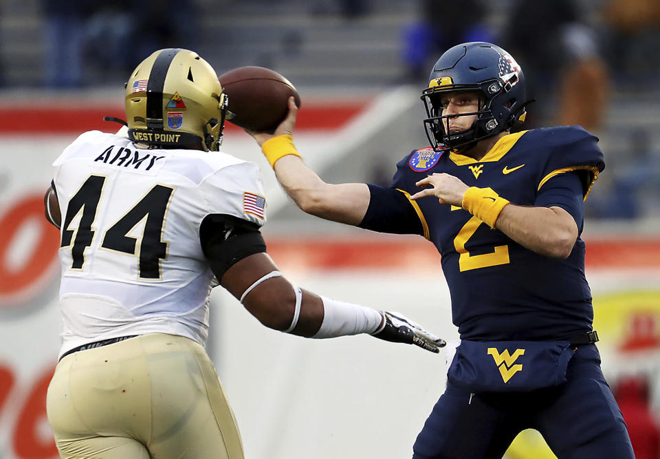 West Virginia quarterback Jarrett Doege (2) throws a pass while under pressure from Army linebacker Nathaniel Smith (44) during the first half of the Liberty Bowl NCAA college football game in Memphis, Tenn., Thursday, Dec. 31, 2020. (Patrick Lantrip/Daily Memphian via AP)